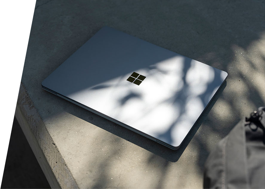 Surface Laptop Go alone outside sitting next to a backpack