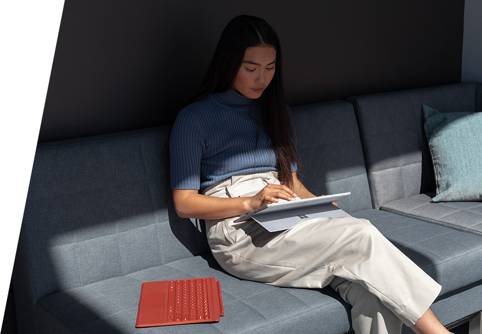 Girl sitting on sofa with Surface Pro 7 in studio mode