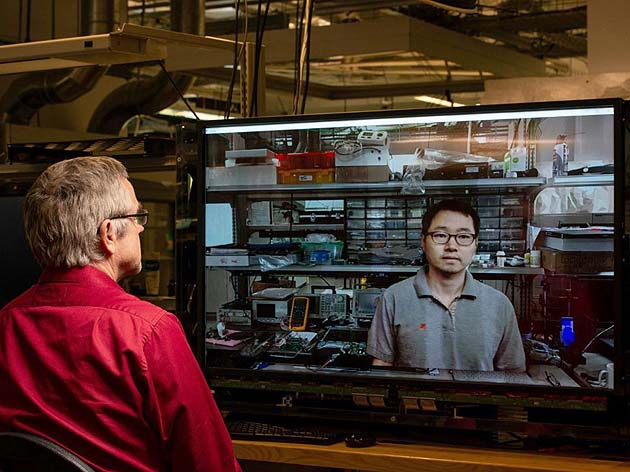 Two researchers conversing by way of displays with embedded cameras