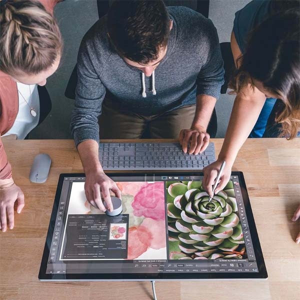 Team collaborating around a Surface Studio