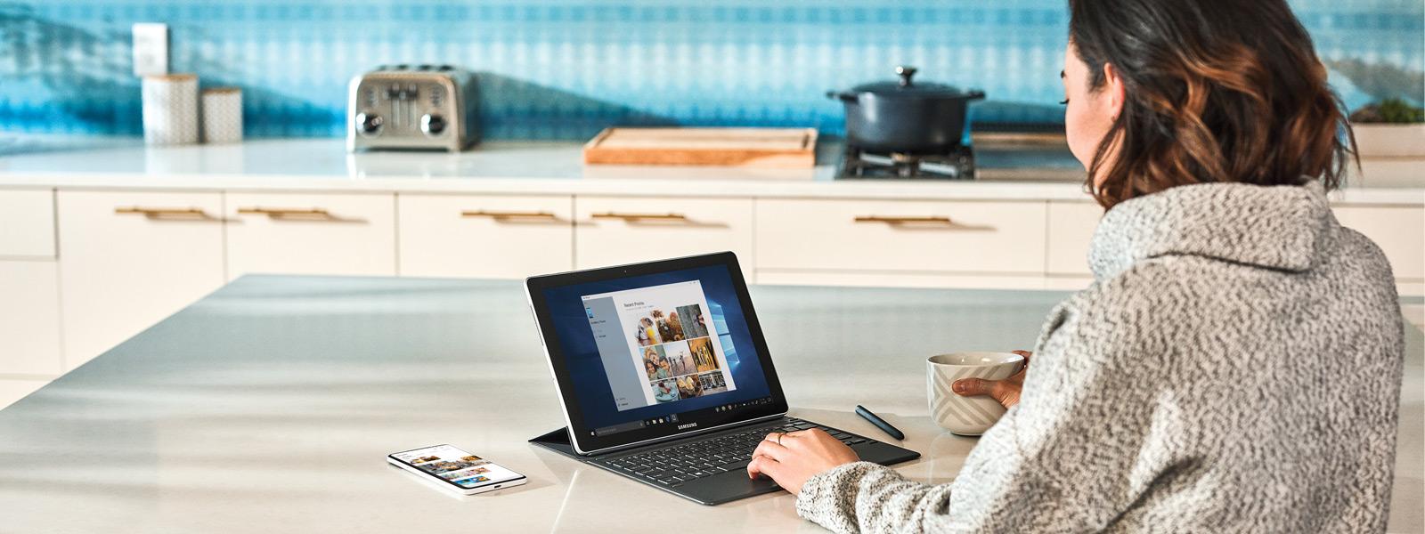 Žena sedící u kuchyňského pultu, používající mobilní telefon a přenosný počítač se systémem Windows 10.