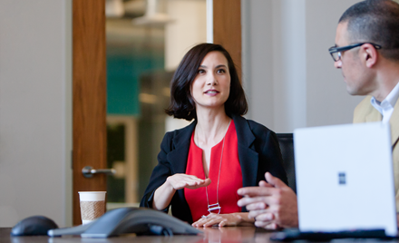 Image for: Image of a woman in a meeting, gesticulating as she speaks.