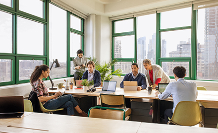 Image of a group of coworkers collaborating in a conference room, each on a variety of different devices.