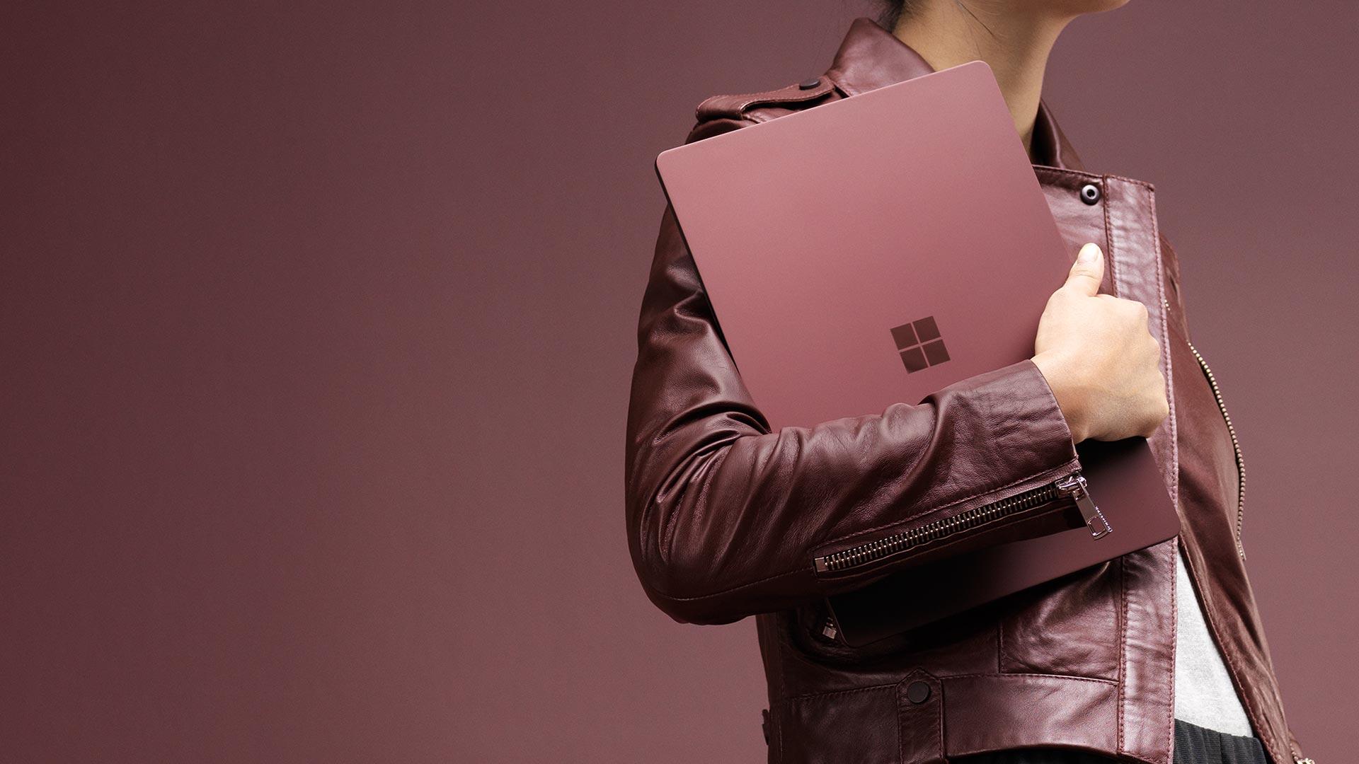 Kvinde, der holder en bordeauxrød Surface Laptop