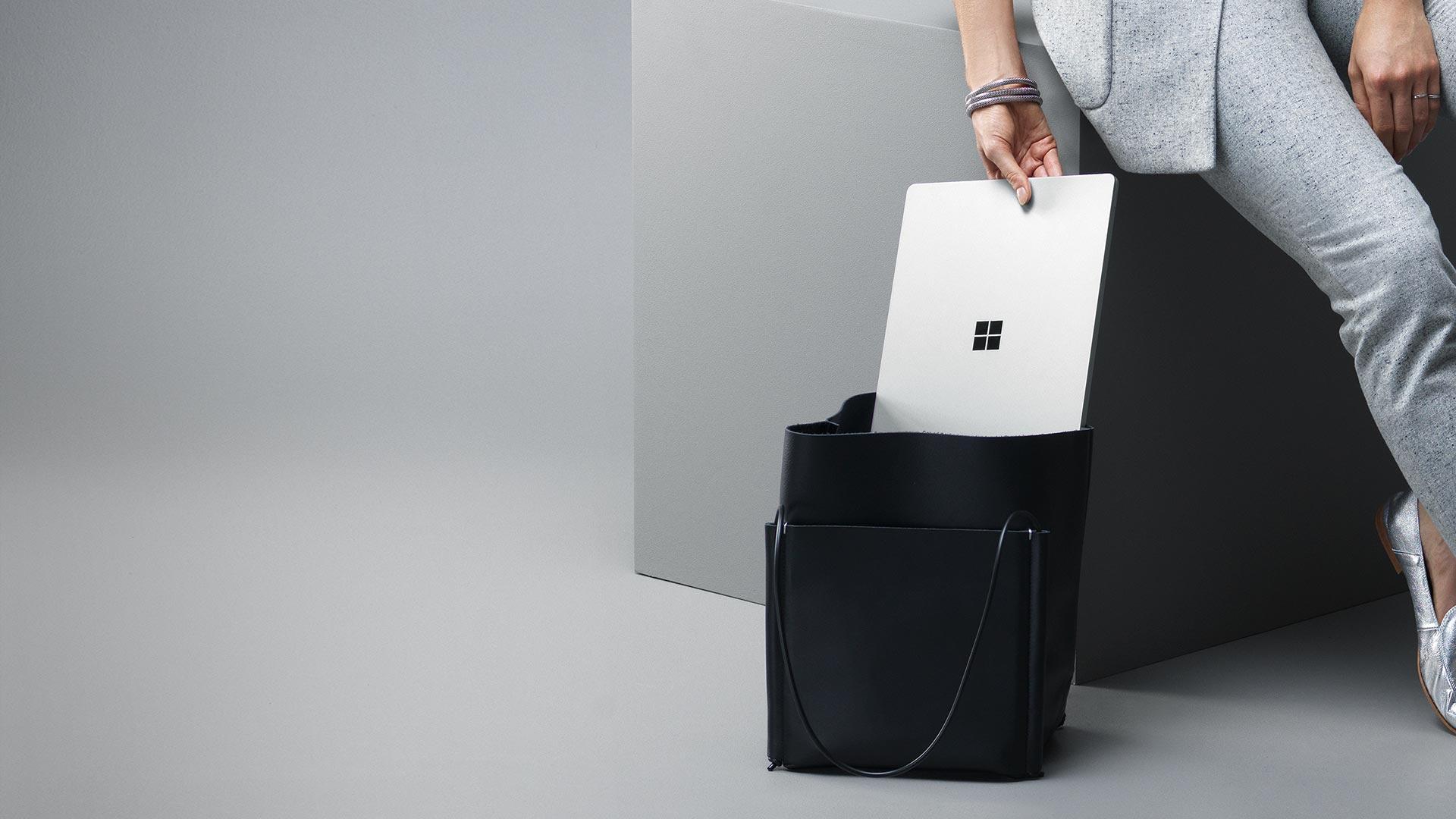 Kvinde, der lægger Surface Laptop (platin) i sin taske.