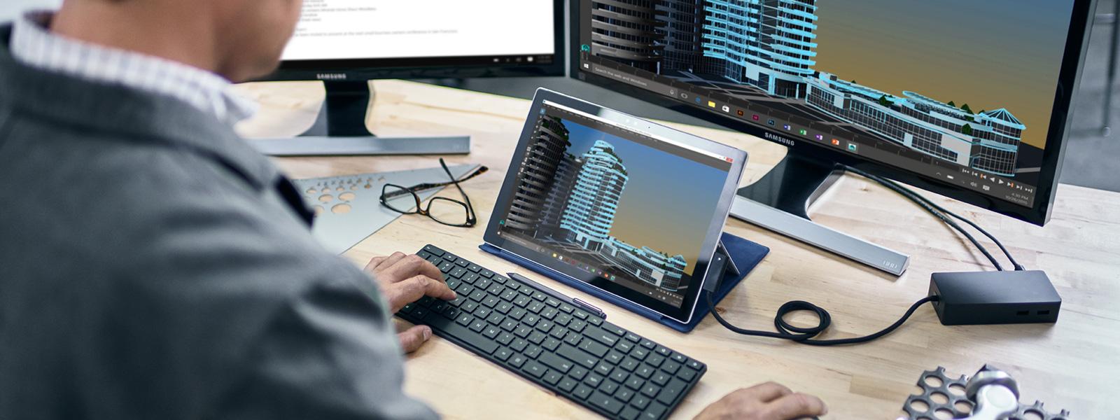 Surface Pro 4, stor skærm og tastatur, der er placeret pä skrivebord.