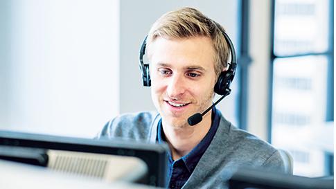 Mann mit einem Headset beantwortet einen Anruf und blickt dabei auf seinen Monitor