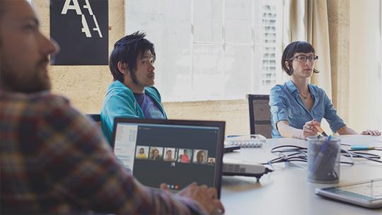 Angestellte sitzen in einer Besprechung um einen Konferenztisch.