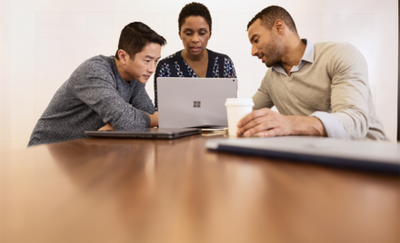 Three adults sitting at a table working together and looking at a Microsoft Surface Book.