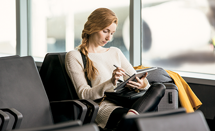 A woman sits in an airport working on her laptop.