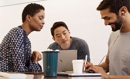 Image of three co-workers collaborating over a laptop on a conference table.