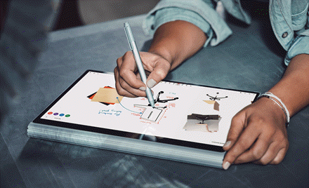 Image of a hand holding a pen and drawing on a tablet that displays Microsoft Whiteboard Preview.