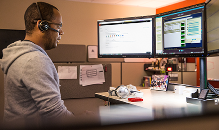 Image of a firstline worker speaking to a colleague over a headset while looking at several computer monitors.