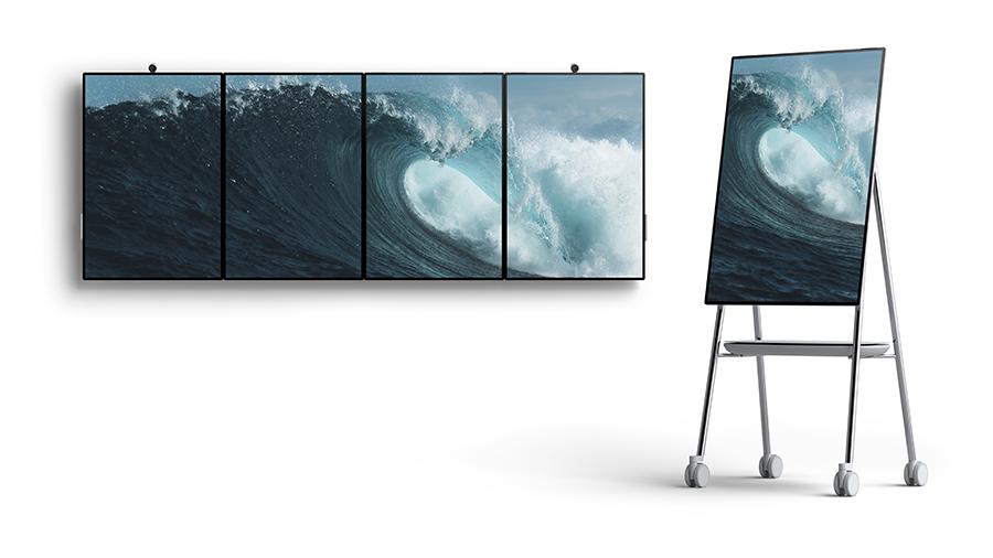 Fünf Surface Hub 2-Bildschirme mit einer Meereswelle. Ein Surface Hub 2 befindet sich auf einem Ständer.