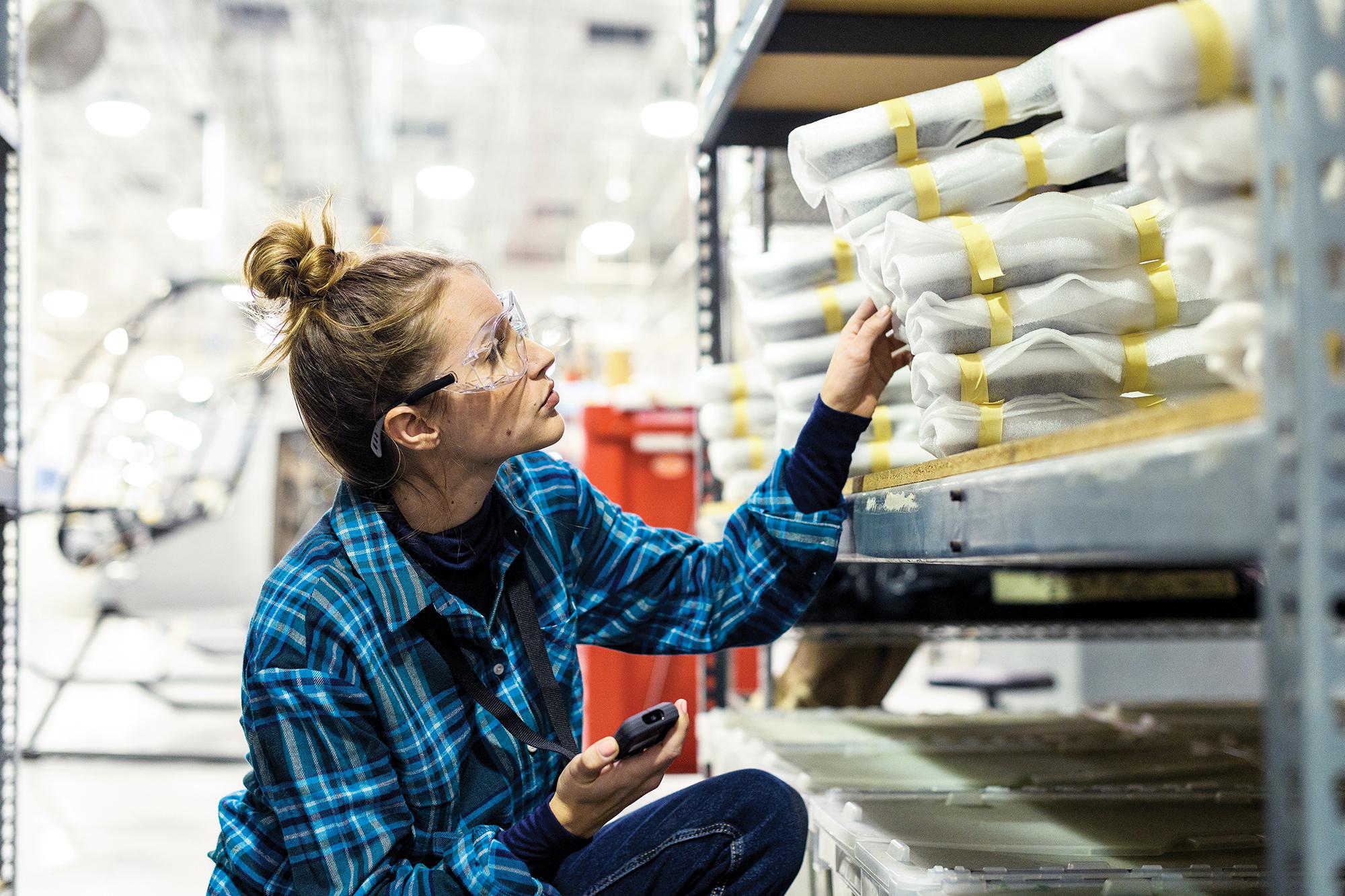 Frau mit Schutzbrille in einer Fabrik