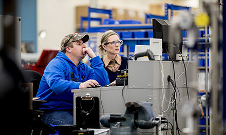 Image of two firstline workers looking at a computer monitor.