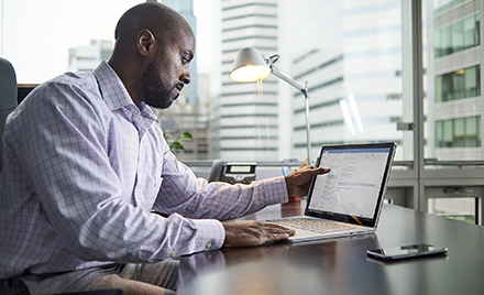 Image of an office worker examining an email on his laptop.