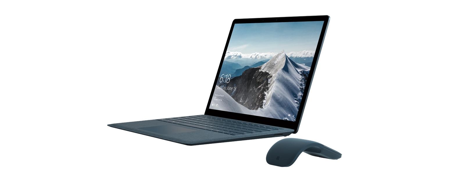 Schrägansicht eines Surface Laptop in Kobalt Blau mit schneebedecktem Berg als Bildschirmhintergrund, daneben eine Arc Touch Mouse in Kobalt Blau.