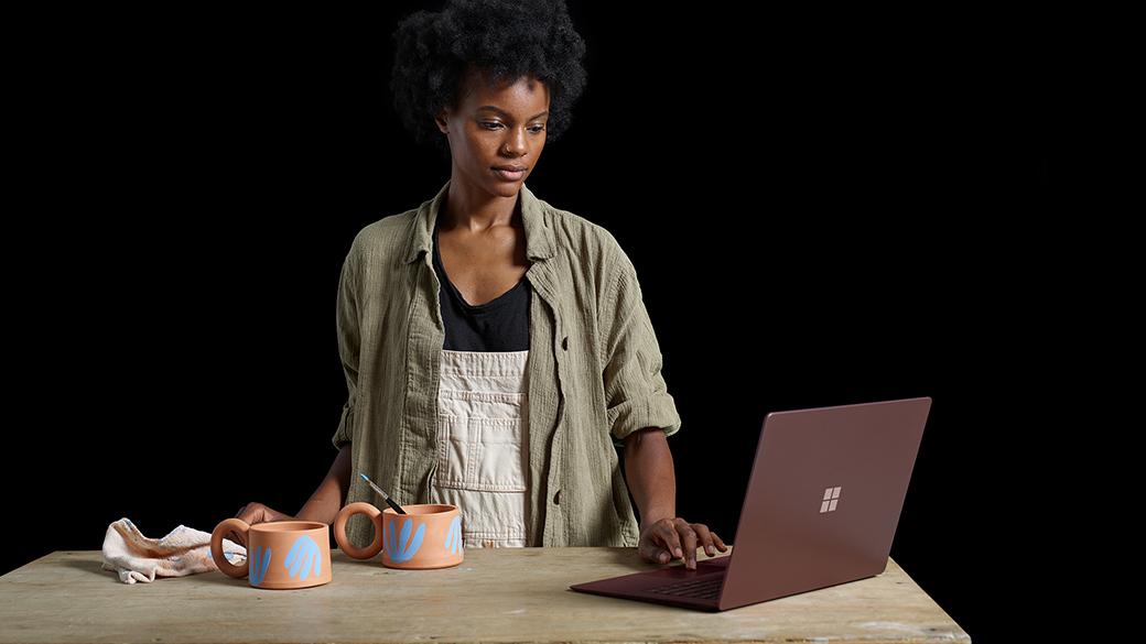 Kenesha mit dem Surface Laptop und Keramikgefäßen