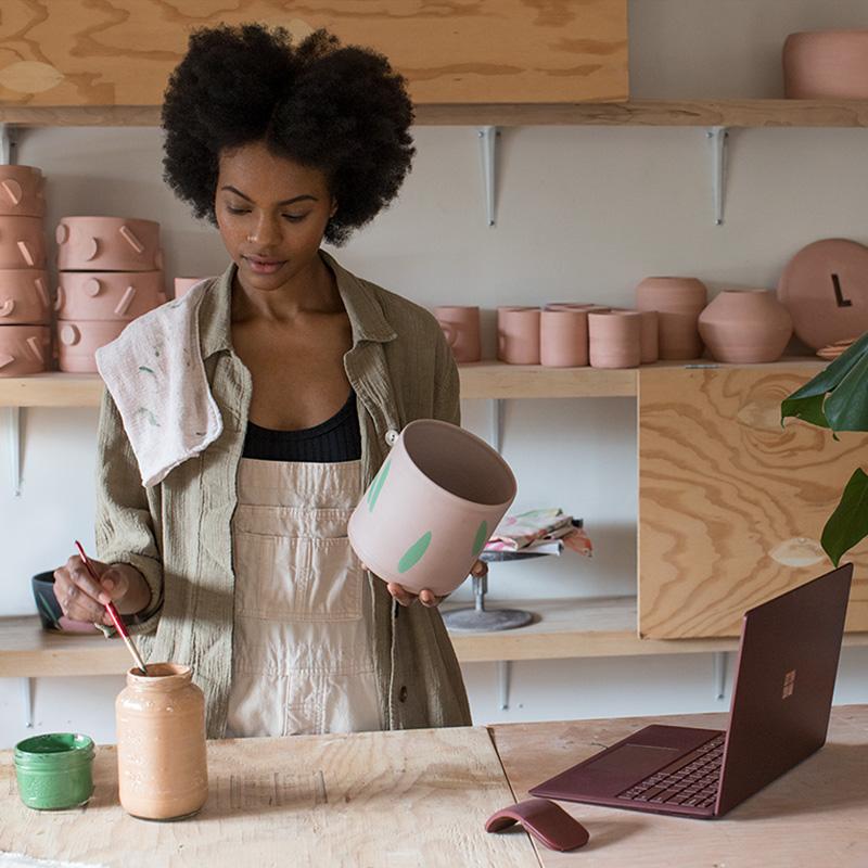 Kenesha Sneed mit Surface Laptop und Surface Arc Mouse in ihrem Keramikatelier