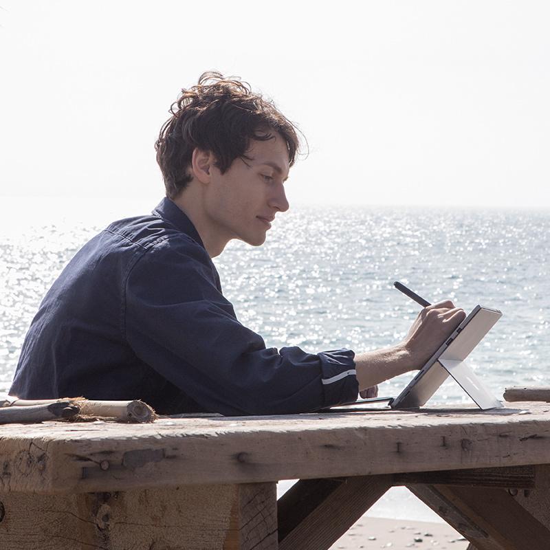 Edsta arbeitet draußen auf dem Surface Pro mit Surface-Stift.
