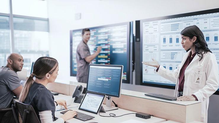 Drei Personen arbeiten in einem Klassenraum mithilfe von Surface-Geräten im Faltmodus und mit dem Surface Hub zusammen.