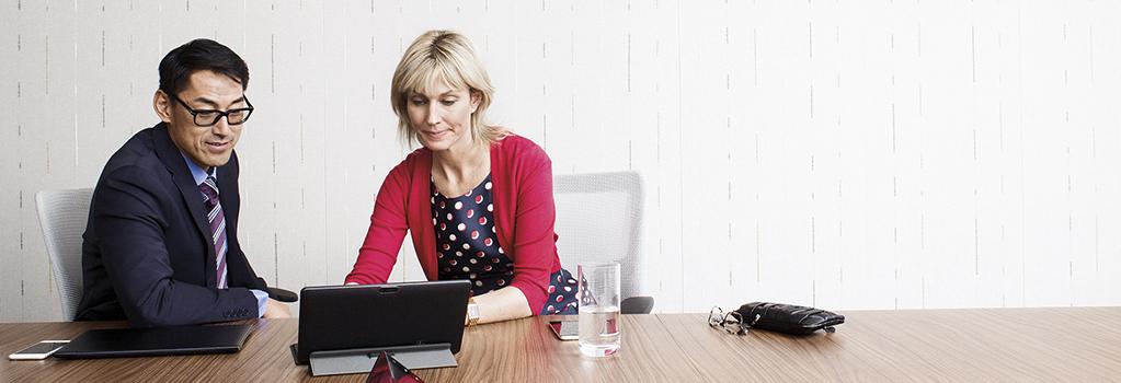 Ein Mann und eine Frau in einer Businessumgebung, die auf einen Computer auf einem Tisch schauen