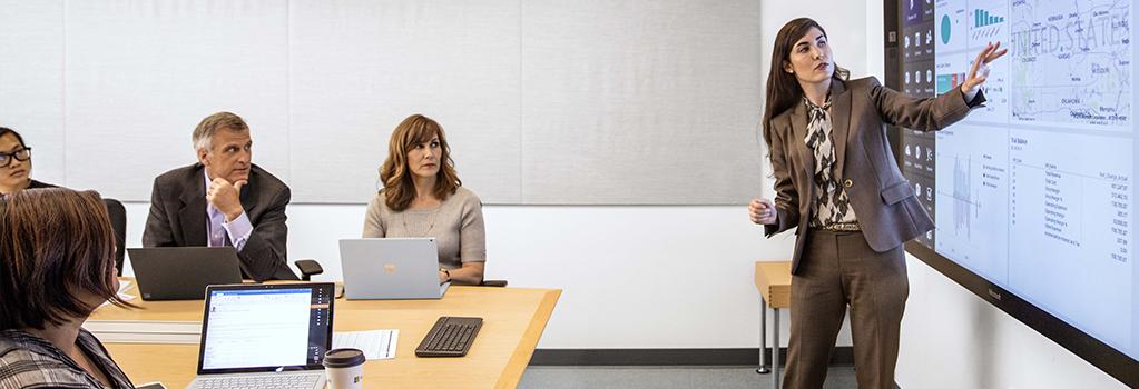 Eine Frau zeigt auf einen Großbildschirm und spricht zu einer Gruppe von Personen, die am Laptop arbeiten.