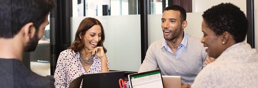 Eine Gruppe von Personen, die lachend und diskutierend um einen Tisch sitzen und an ihren Laptops arbeiten