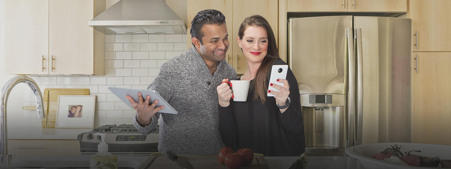 Ein Paar steht zusammen in einer modern eingerichteten Küche. Der Mann hält ein Tablet und die Frau hält ein Handy. Beide lachen und schauen gemeinsam auf den Bildschirm des Handys.