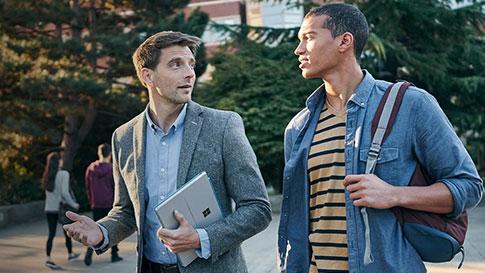 Zwei Männer, die spazieren gehen und sich dabei unterhalten. Der eine hält seinen Rucksack fest, während der andere einen Surface Pro4 in der Hand hat.
