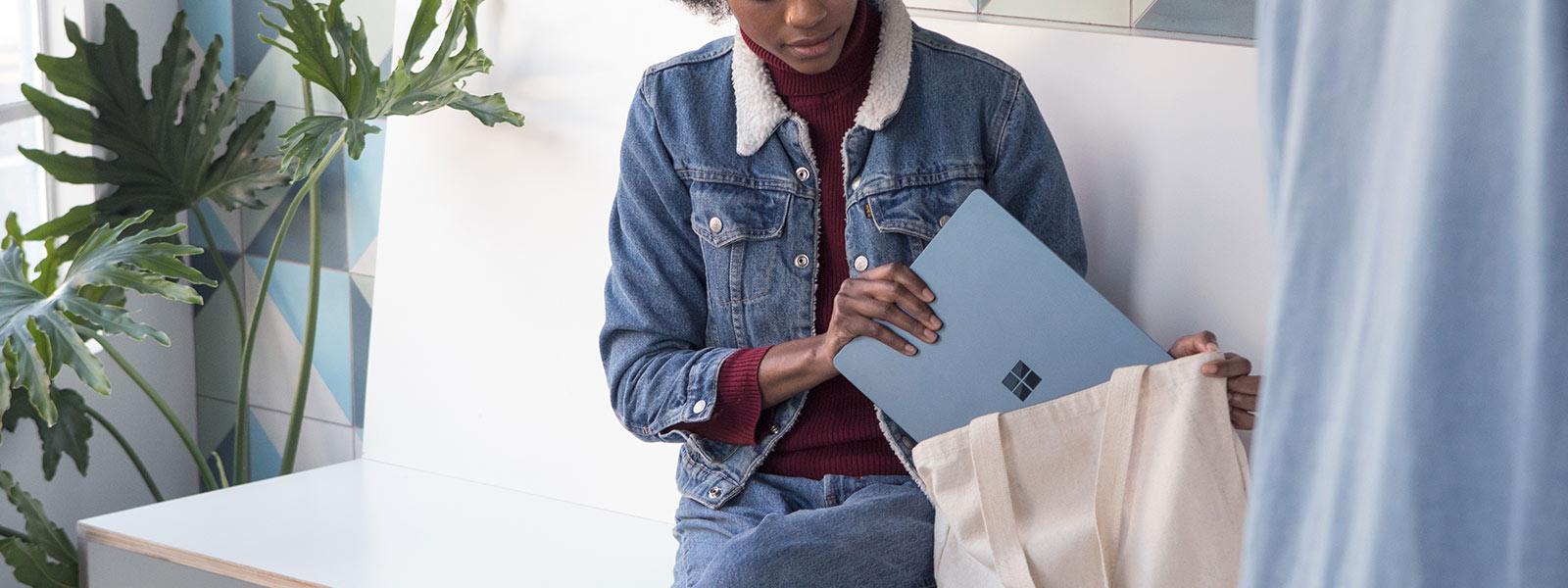 Frau verstaut Surface Laptop in ihrer Tasche.