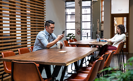 Image of two workers working at separate tables in a casual office environment.