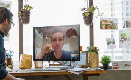 Image of a worker sitting at his desk and holding a video conference call with a coworker.