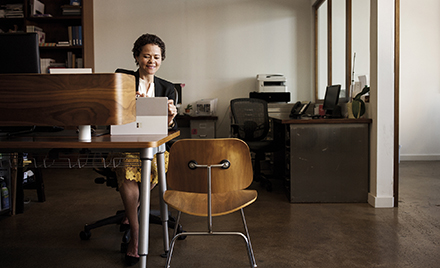 Image of a worker in her office working on a laptop.
