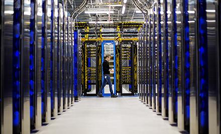 Image of a man walking through a datacenter.
