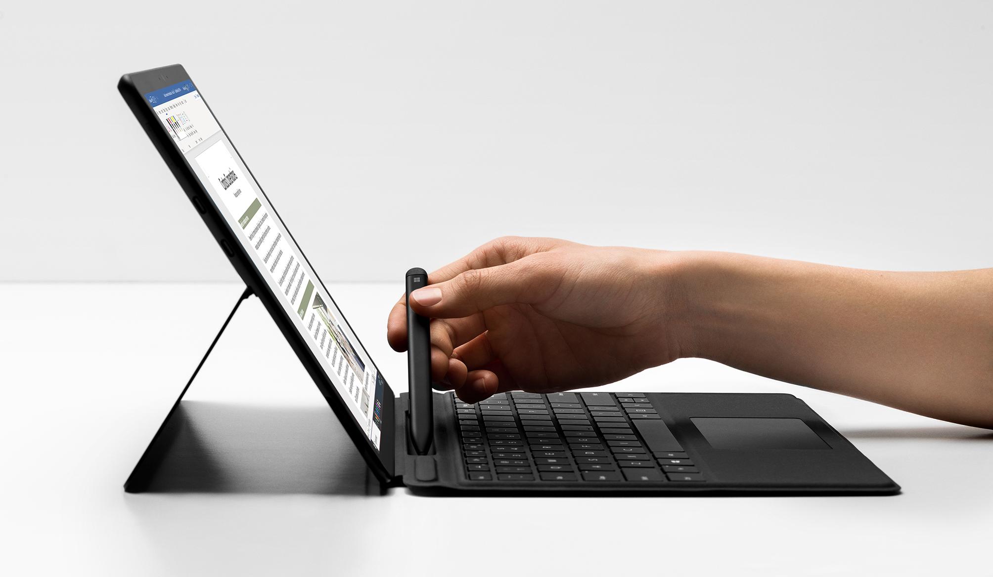 Abbildung einer Hand, die einen Stift aus dem Fach des neuen Surface Pro X nimmt