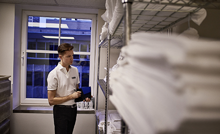 Image of a hotel worker checking supplies in a supply room.