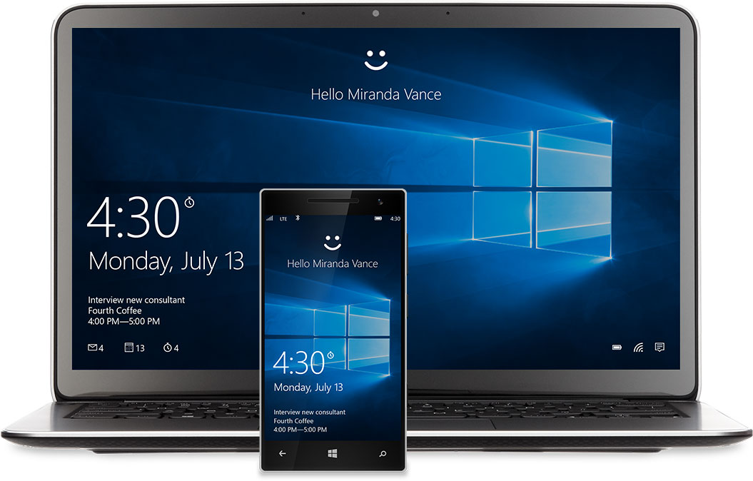 """A laptop and phone with the Windows 10 Start screen on the display. There's a smiley face at the top of each above the words, """"Hello Miranda Vance�"""