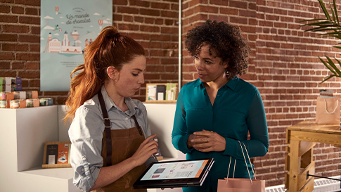 A photo of two women in a retail store. One is a sales assistant showing the customer something on a tablet