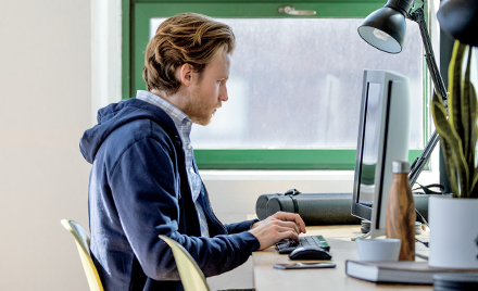 Image of a worker sitting at his desk, hands hovering over his keyboard.
