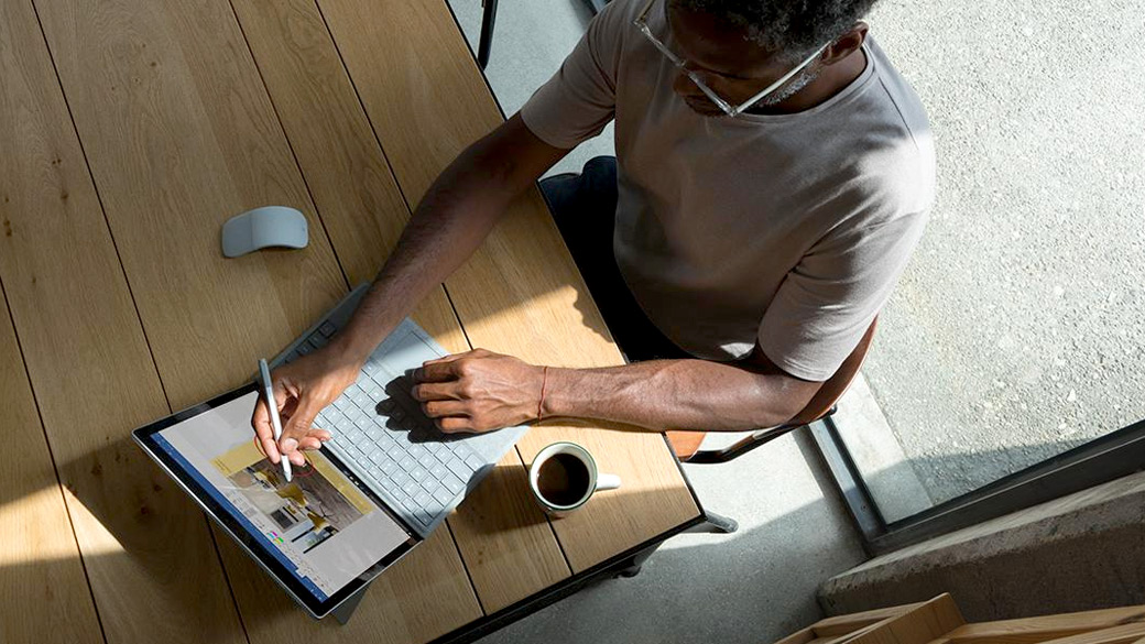 Man sits at desk using Surface Pen on Surface Laptop with Arc mouse