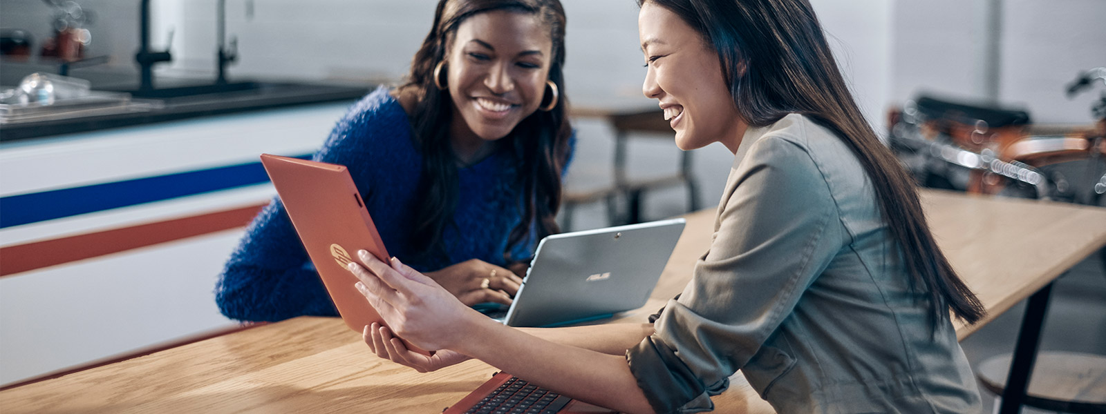 Two women seated at table, looking at a tablet screen being help up between them by the other woman