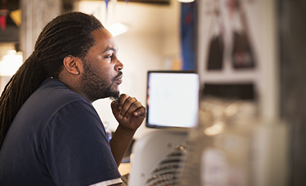 Image of a tech worker stroking his beard and looking at a computer monitor.