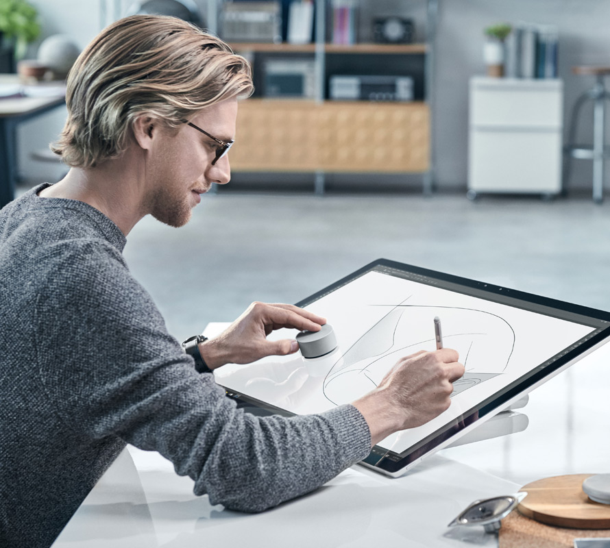 A man uses a Surface Pen on Surface Studio