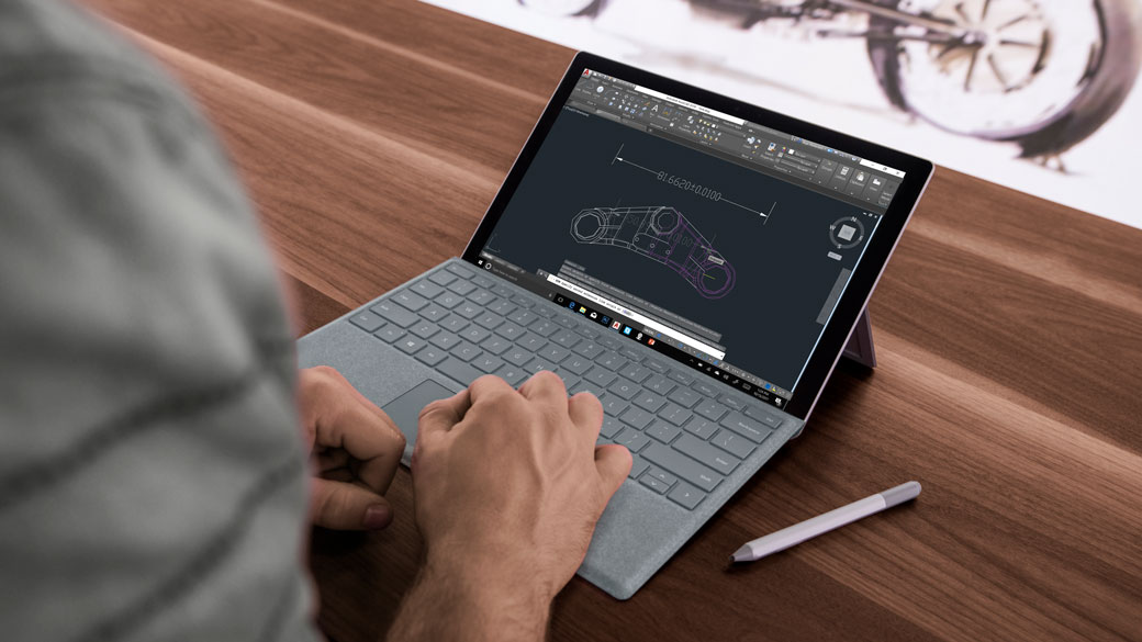 Image of Surface Pro screen in laptop mode with a pen to the side and hands on the keyboard