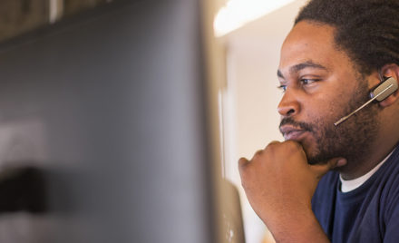 Image of a firstline worker looking at several computer monitors.