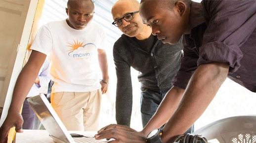 Satya Nadella looking at a laptop with 2 young men