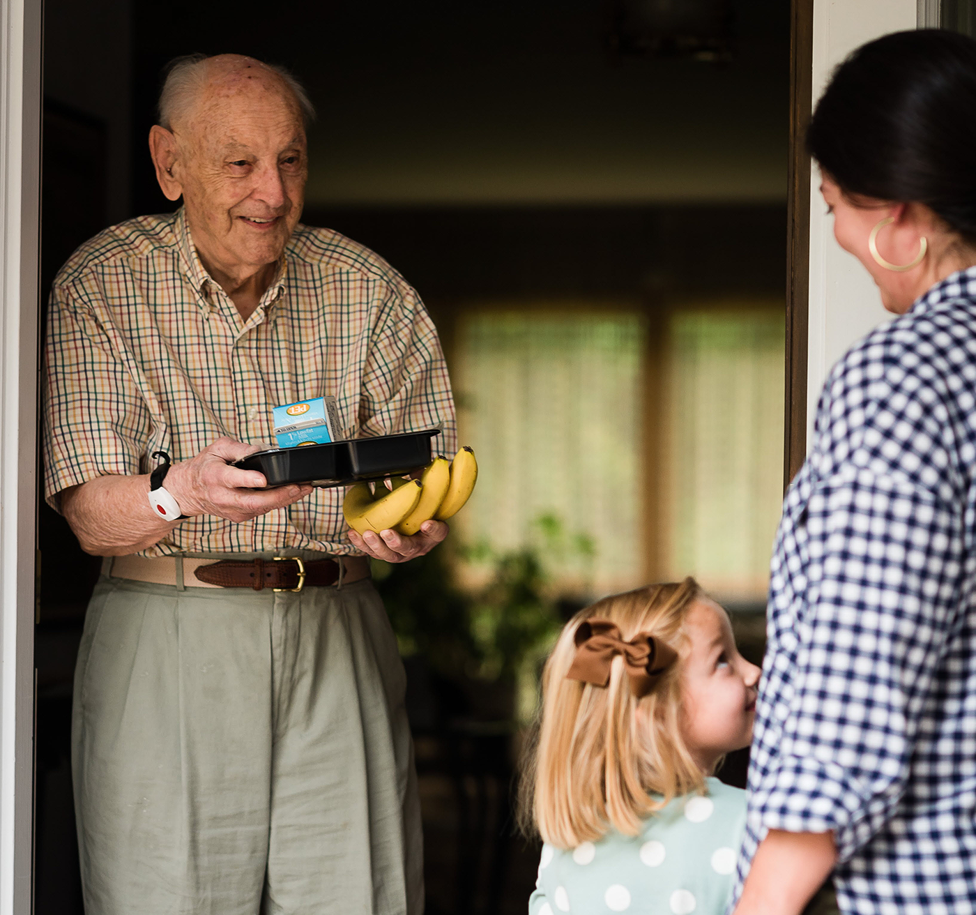 Image of a man receiving goods from Meals on Wheels.