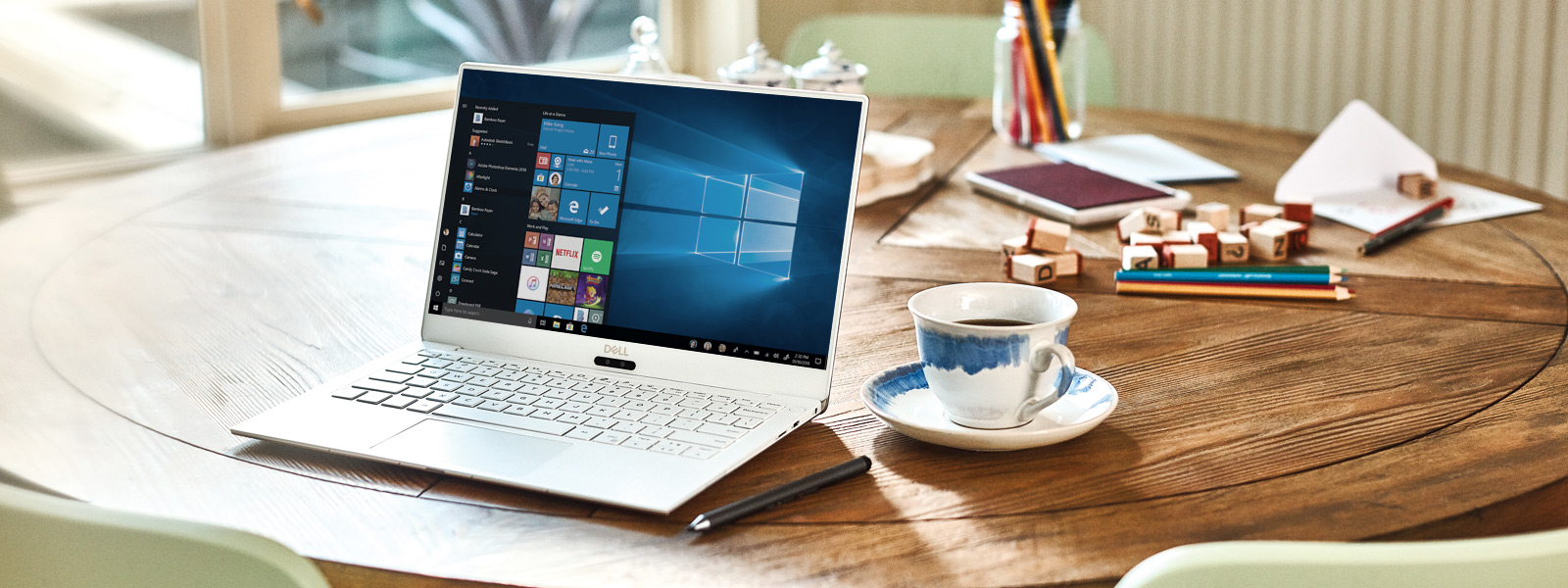 A Dell XPS 13 9370 sits open on a table with a Windows 10 start screen.